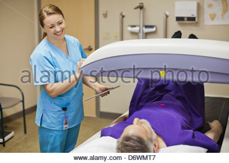Happy female doctor with senior male patient getting a bone density scan - Stock Photo