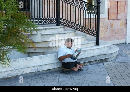 Mexican man with deformed legs and feet sitting on a skateboard and reading a newspaper, Cancun, Quintana Roo, Mexico - Stock Photo