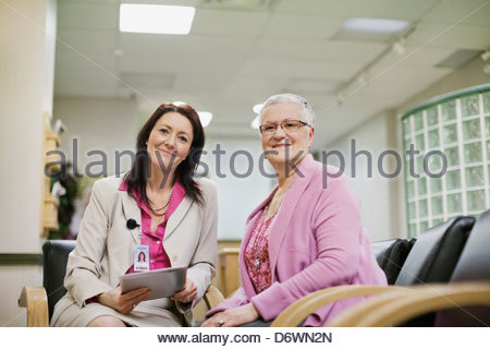 Portrait of happy mature female doctor with senior patient in hospital - Stock Photo
