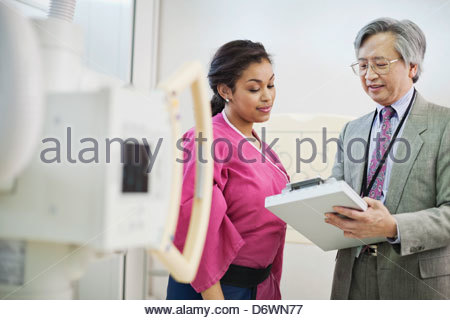 Senior male doctor explaining reports to female patient - Stock Photo