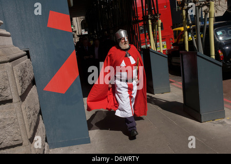 A lunchtime gentleman wearing the red theme of St George, walks through the City of London on St George's Day (April - Stock Photo