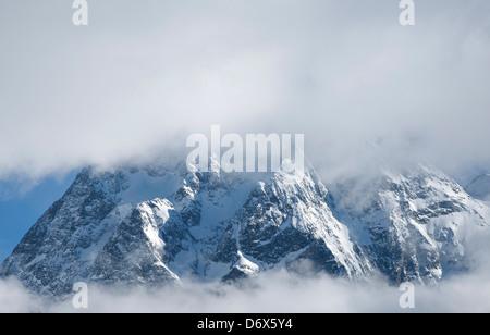 Mont Collon poking through cloud above Arolla - Stock Photo
