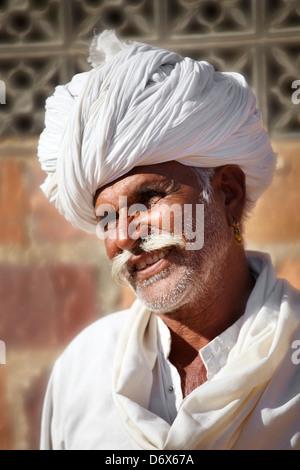 Rajasthani india - portrait of smiling hindu man with moustache wearing white turban - Stock Photo