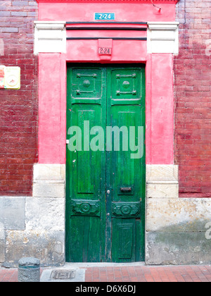Green wooden doors and pink and red brick building, Bogota, Colombia - Stock Photo