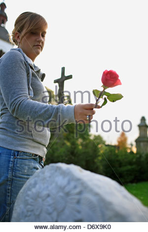 Woman with a rose on a gravestone, Bonn, Germany - Stock Photo