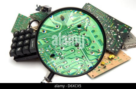 Concept photo showing digital computer parts discarded in garbage pile examined with maginfying glass - Stock Photo