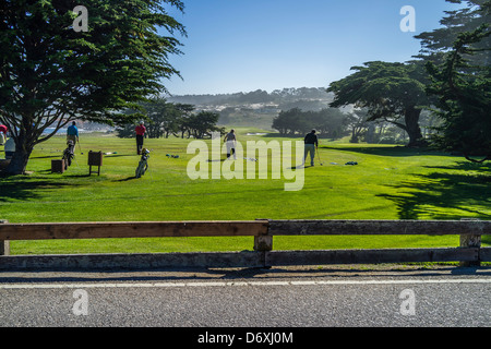 Golfers tee off at a driving range on the Monterey Peninsula near Pebble Beach in Northern California, USA. - Stock Photo
