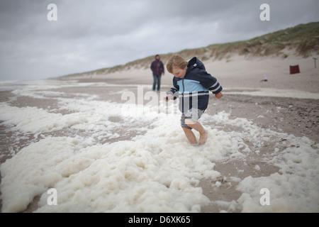 Hvide Sande, Denmark, a boy running barefoot on the beach - Stock Photo