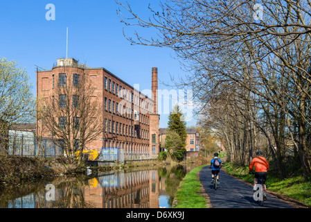 Cyclists on the banks of the Leeds to Liverpool Canal on the outskirts of Leeds near Oddy Locks, West Yorkshire, - Stock Photo