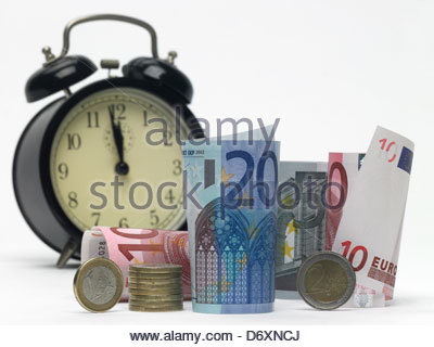 5,10 and 20 Euro notes rolled up standing and lying with alarm clock and euro coins