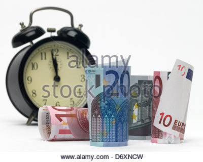 5,10 and 20 Euro notes rolled up standing and lying with alarm clock