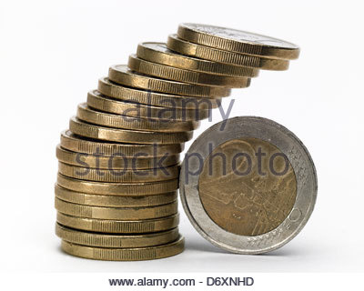 Stack of one Euro coins with two Euro coin leaning against them - Stock Photo
