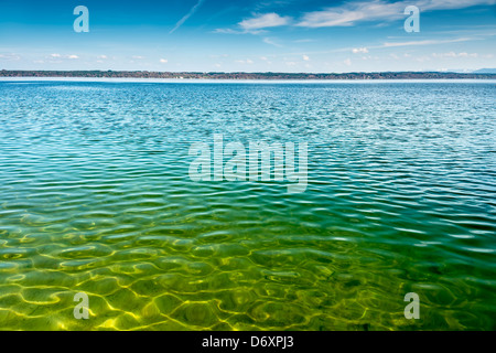 View of Lake Starnberg in Tutzing in Germany on the water, the other shore and blue sky with white clouds - Stock Photo