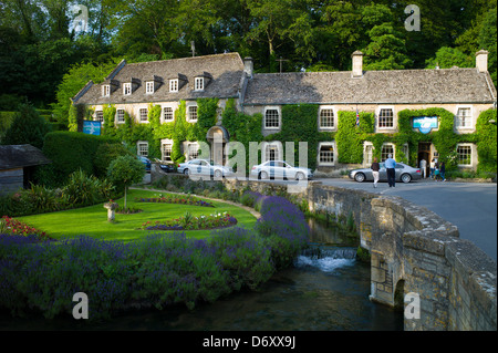 Swan Hotel and River Coln at Bibury in The Cotswolds UK. L to R: Audi A8, Mercedes C Class (2 silver cars), BMW - Stock Photo