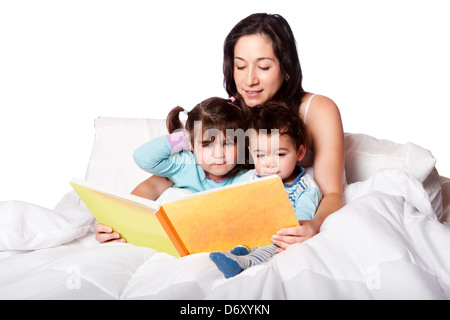 Mother reading bed time story book to daughter and son kids in bed, isolated. - Stock Photo