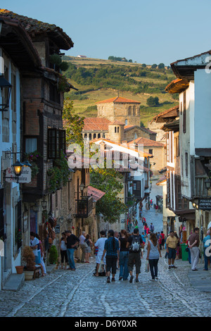 Tourists walk past medieval buildings along cobbled street of Calle Del Canton in Santillana del Mar, Cantabria, - Stock Photo