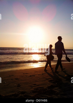 Silhouette of couple walking on beach at sunset - Stock Photo