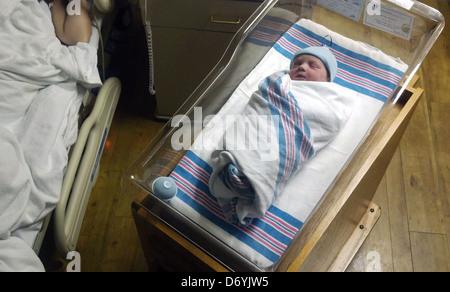 Caucasian newborn baby sleeping in bassinet - Stock Photo