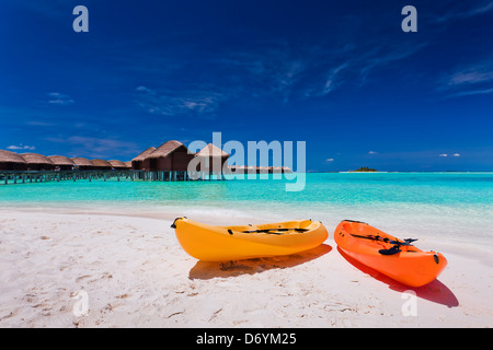 Two colourful kayaks on the tropical beach - Stock Photo