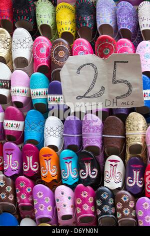 traditional maroccan slippers for sale on a wall in Fez, Marocco - Stock Photo