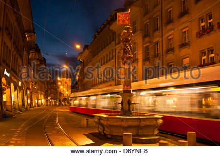 A tram passes by the Musketeer Fountain (Schutzenbrunnen) on Marktgasse with the Prison Tower (Kafigturm) in background, - Stock Photo