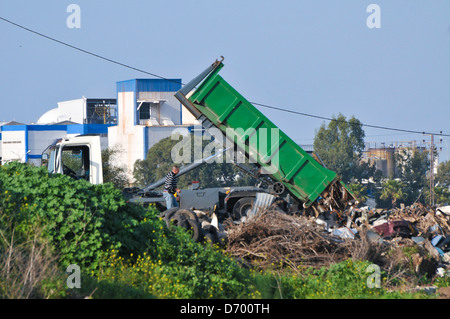 Illegal Littering - a truck dumps trash in a vacant field - Stock Photo