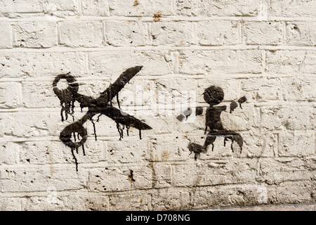 street art showing man being chased by scissors - Stock Photo