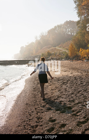 A woman walks by herself on a Lake Michigan beach in autumn. - Stock Photo