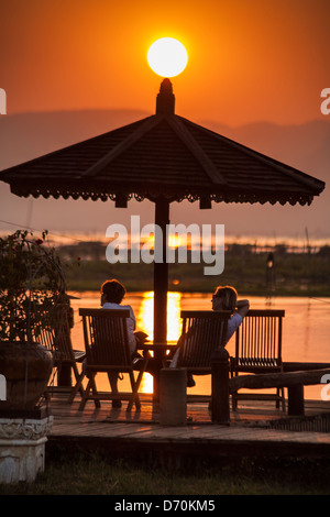 Tourists relaxing during a sunset over Inle Lake, Nyaung Shwe, Shan State, Myanmar, (Burma) - Stock Photo