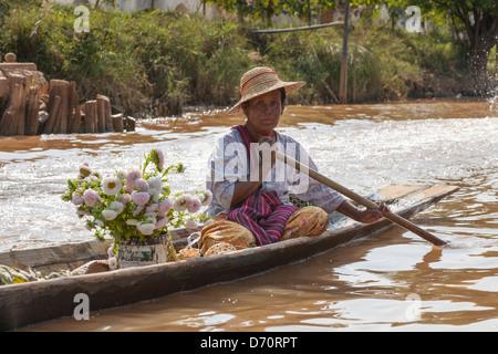 Woman rowing a canoe, Ywama village, Inle Lake, Shan State, Myanmar, (Burma) - Stock Photo
