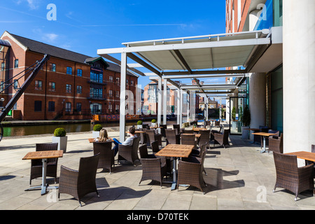 Couple siting on terrace of DoubleTree Hotel overlooking Leeds-Liverpool Canal, Granary Wharf, Leeds, West Yorkshire, UK Stock Photo