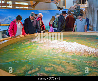 Tourists viewing a three dimensional topographic map at the Denali National Park Visitors Center, Denali National - Stock Photo