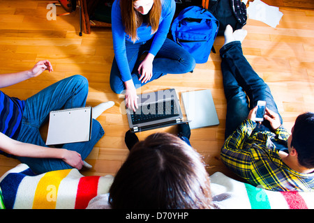 overhead view of a group of teens on the floor working on a project using various means and technologies.  multi - Stock Photo
