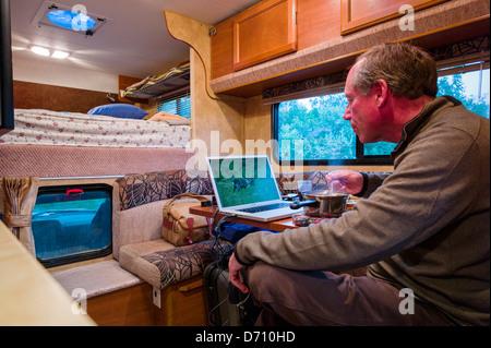 Professional photographer editing digital photographs on laptop computer inside a camper truck, Denali National - Stock Photo