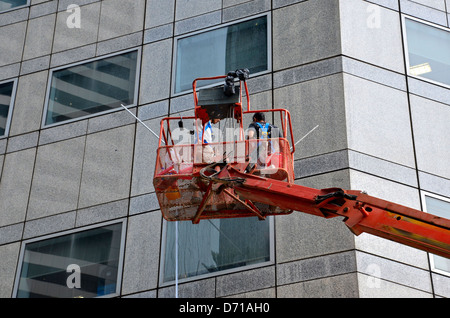 Cleaning skyscraper window and wall - Stock Photo
