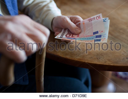 Senior woman holding euros - Stock Photo