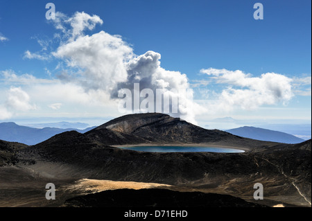 Smoke rising from the Te Maari crater, Mount Tongariro with Blue Lake in the foreground. Tongariro Alpine Crossing, - Stock Photo