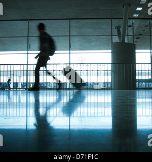 abstract airport and silhouette of walking person with luggage - Stock Photo