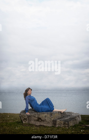 a girl in a blue dress is lying on a stone - Stock Photo