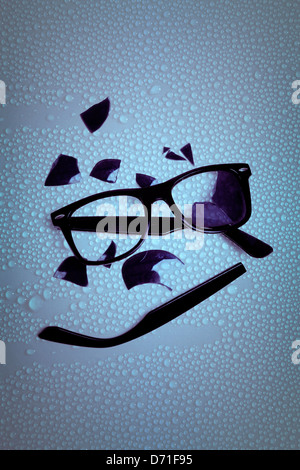 broken sunglasses on a wet table - Stock Photo