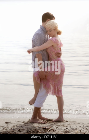 a couple on the beach, hugging each other - Stock Photo