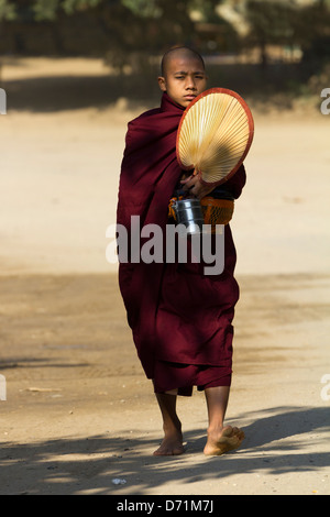 Novice monk with fan, lunchbox and collection bowl in Bagan, Myanmar 3 - Stock Photo
