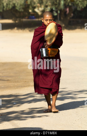 Novice monk with fan, lunchbox and collection bowl in Bagan, Myanmar 2 - Stock Photo