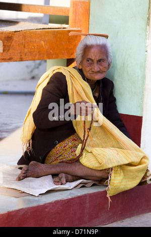 Wizened old woman with rosary beads in a Bagan pagoda, Myanmar - Stock Photo
