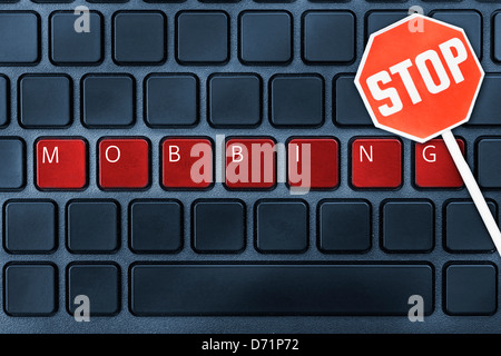 The word Harassment on a computer keyboard and stop sign, on-line harassment - Stock Photo