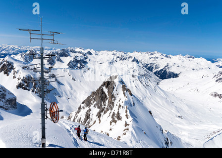 Two skiers admiring the view near the top of the Valluga cable car, high above St Anton in Austria - Stock Photo