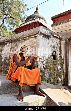Sadhu playing flute in pashupatinath temple in Kathmandu Nepal - Stock Photo
