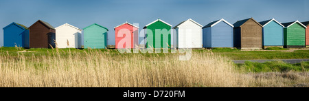 A row of colourful beach huts on the shore at Calshot in Hampshire. - Stock Photo