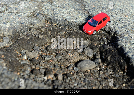 Miniature car in blow hole on the street, symbolic photo street damages