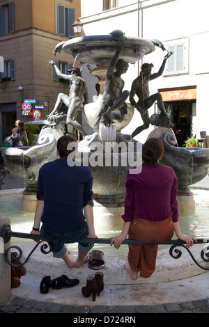 Rome Tourists looking fountain of turtles Italy - Stock Photo
